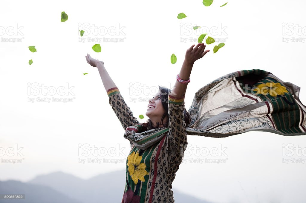 Happy young woman flying leafs in air towards sky. stock photo
