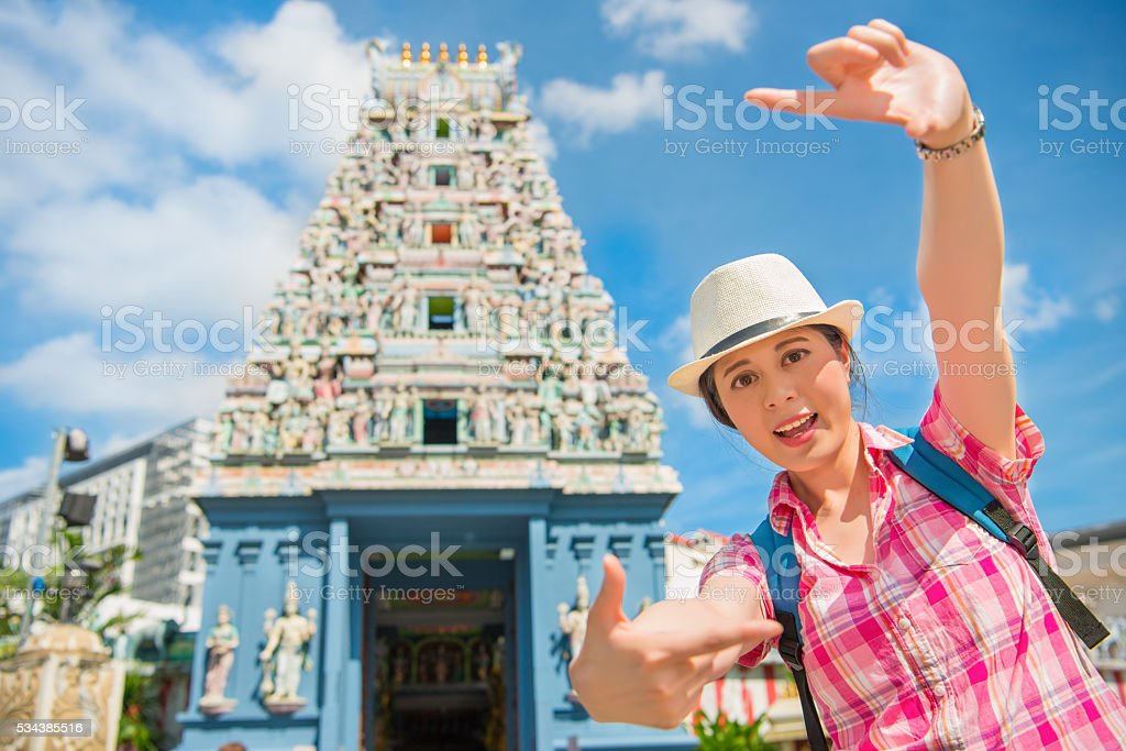 Happy young woman framing in Sri Mariamman Temple, Singapore stock photo