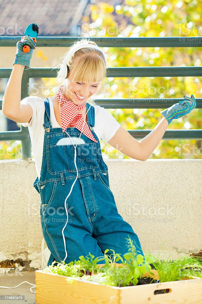 Happy Young Woman Gardening on a balcony. royalty-free stock photo