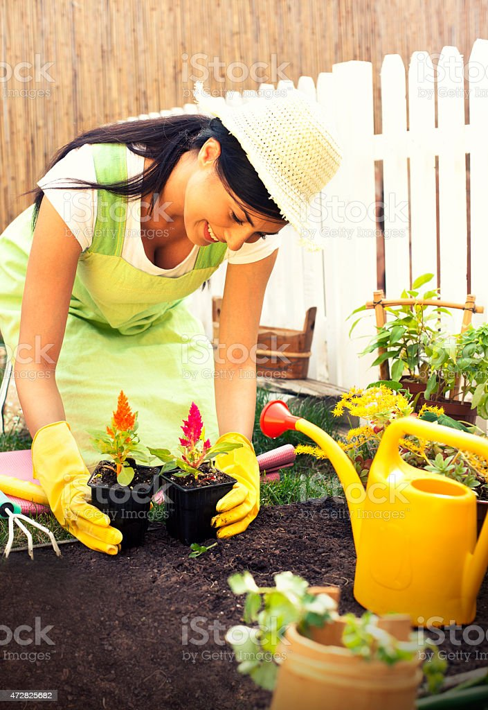 Happy young woman gardening stock photo
