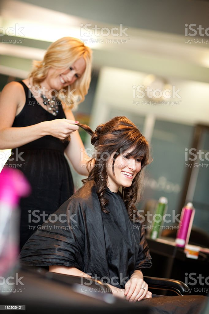 Happy Young Woman Getting Hair Styled as Updo in Salon royalty-free stock photo