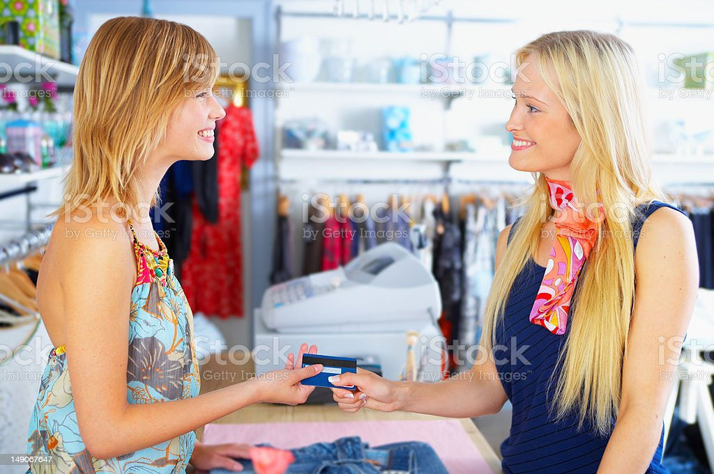 Happy young woman giving credit card to shopkeeper royalty-free stock photo