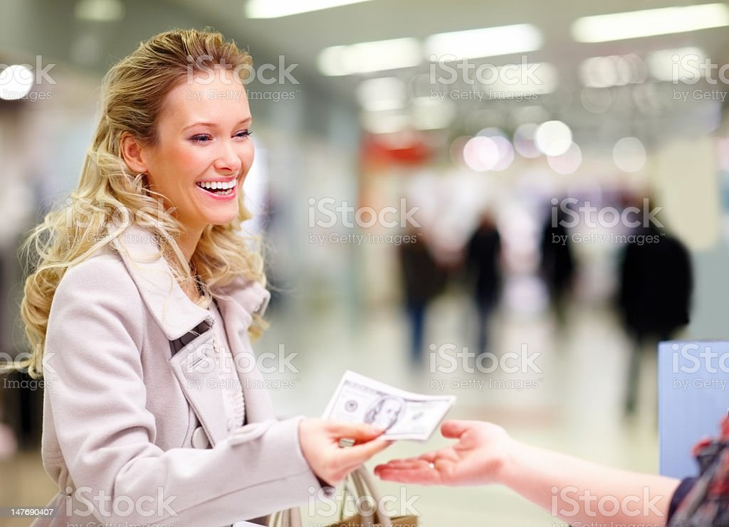 Happy young woman giving money at cash counter royalty-free stock photo
