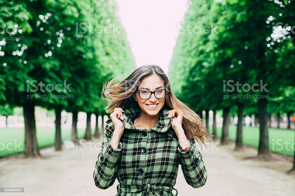 Happy young woman having fun in the park stock photo