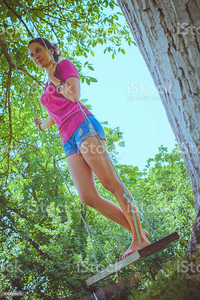 Happy young woman having fun on a swing in park stock photo