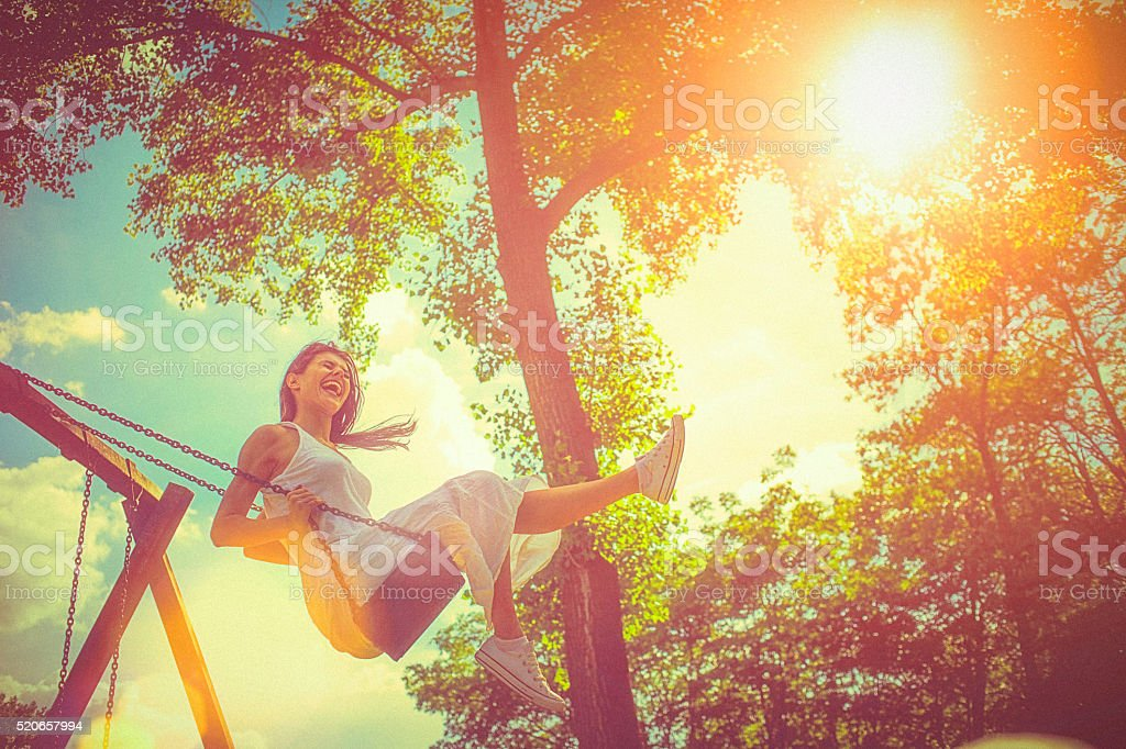 Happy young woman having fun on the swing stock photo