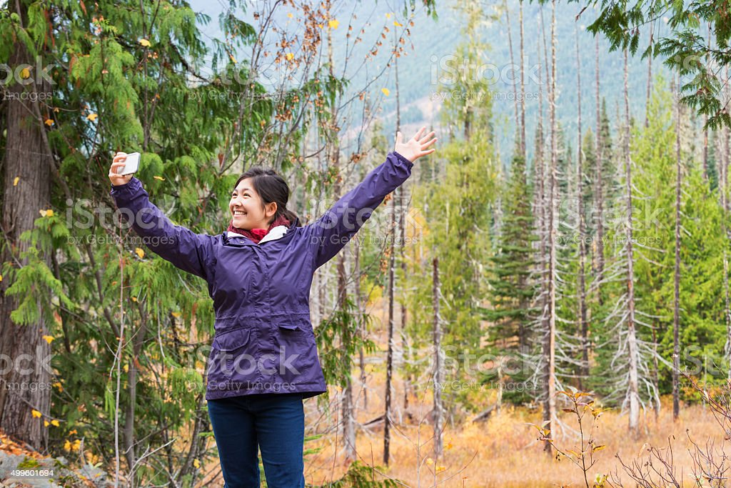 Happy Young Woman Hiker Taking Selfie in Alpine Mountain Forest stock photo