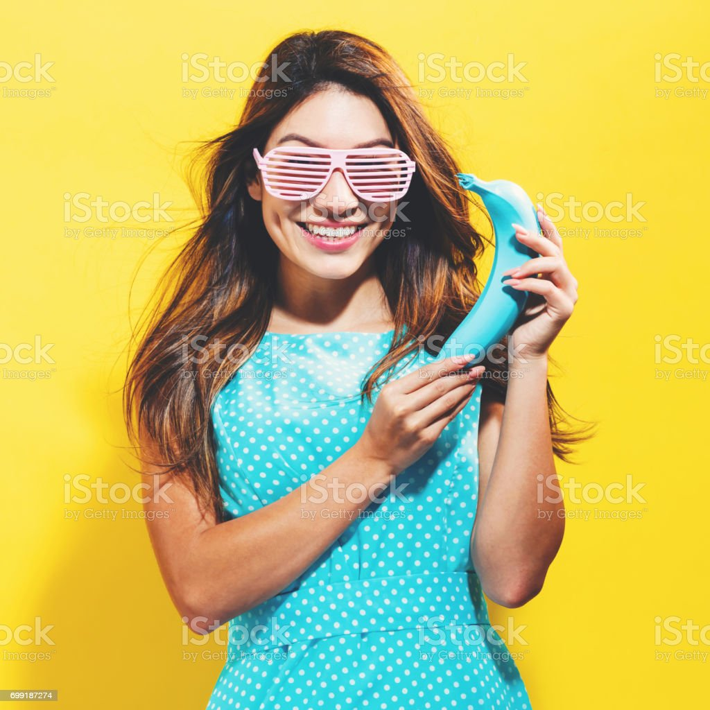 Happy young woman holding a colored banana stock photo