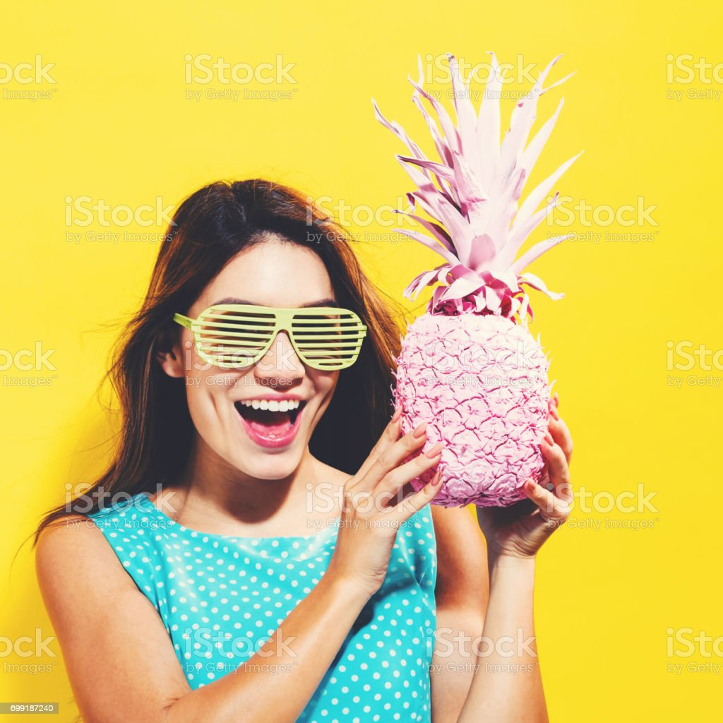 Happy young woman holding a pineapple stock photo