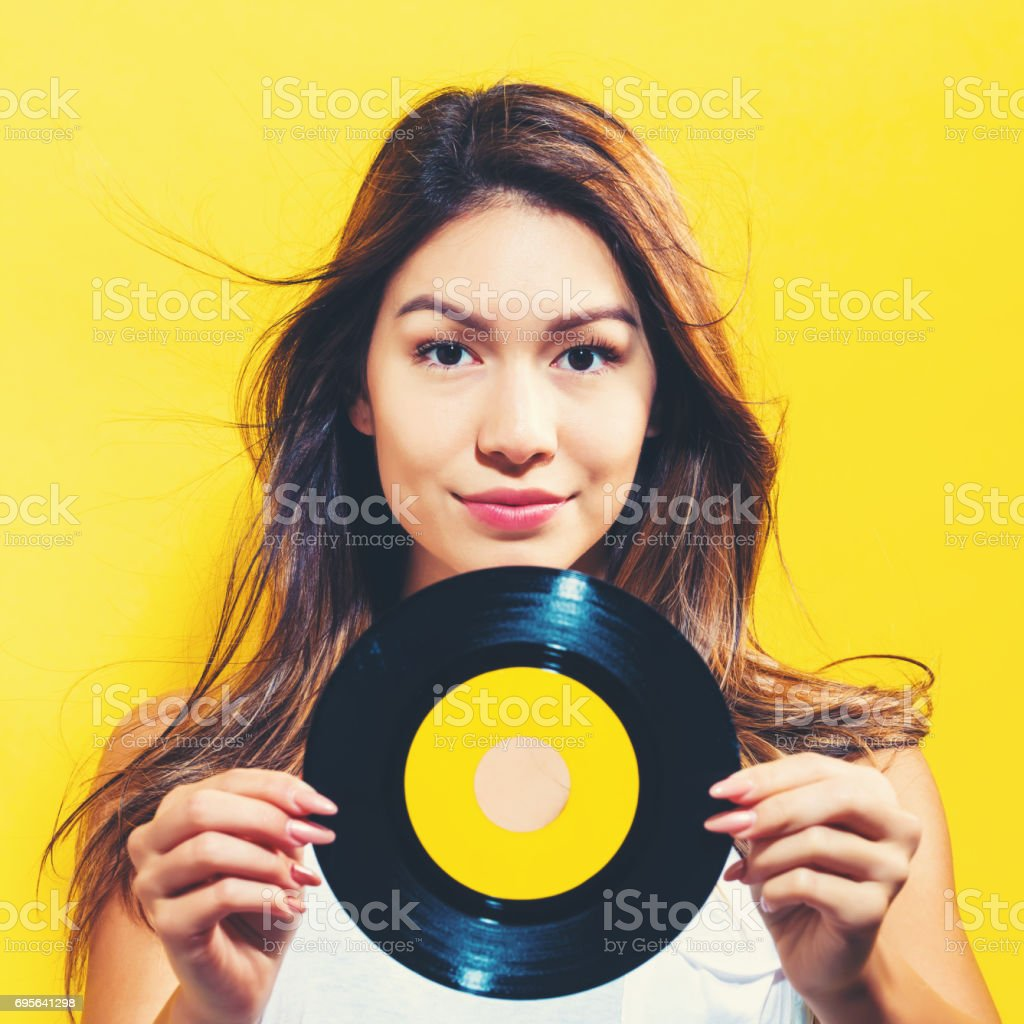 Happy young woman holding a record stock photo