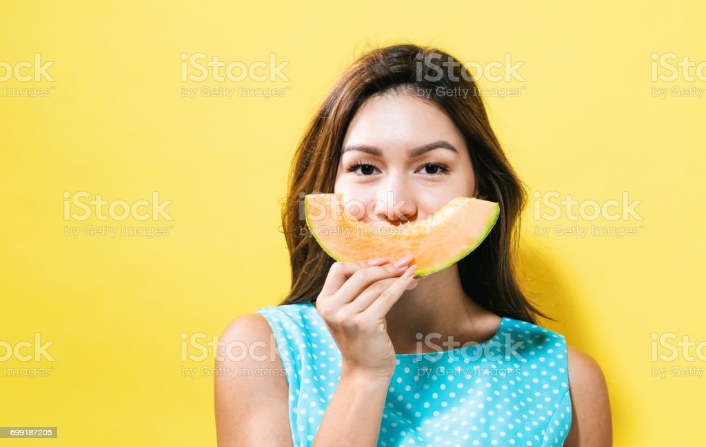Happy young woman holding a slice of cantaloupe stock photo