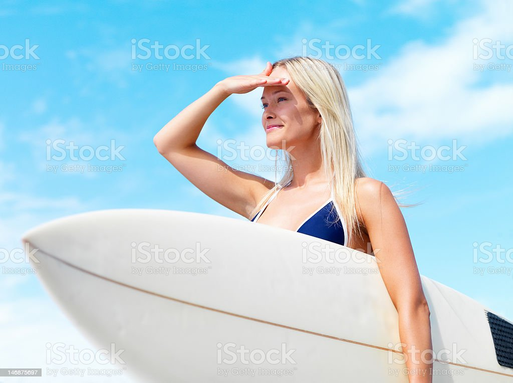Happy young woman holding a surfboard and shielding eyes royalty-free stock photo