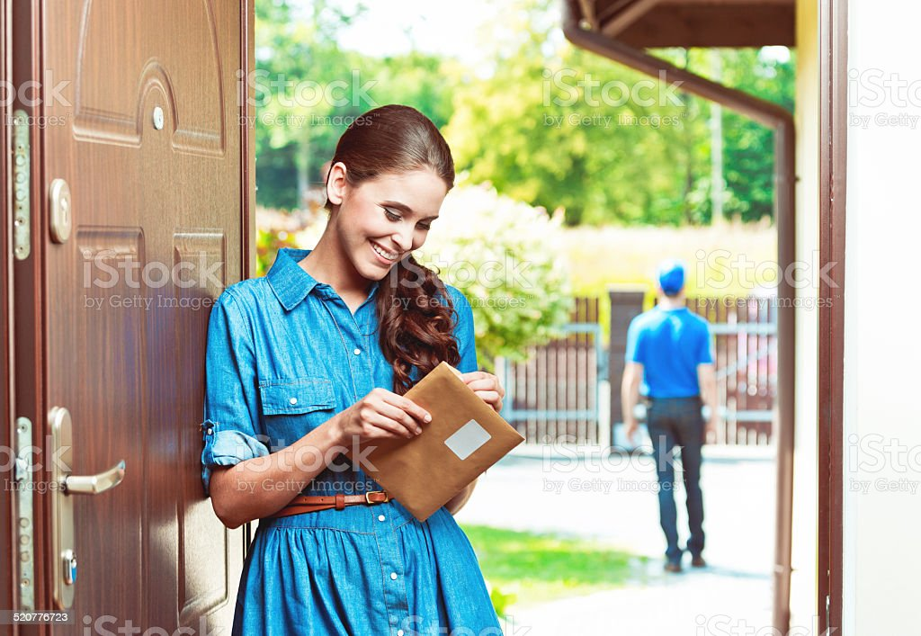 Happy young woman holding an envelope stock photo