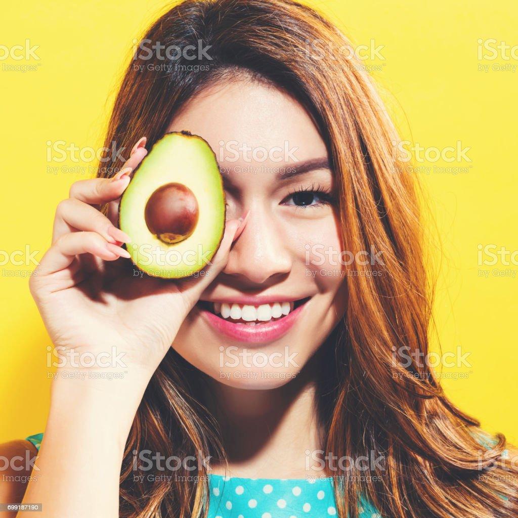 Happy young woman holding avocado halve stock photo