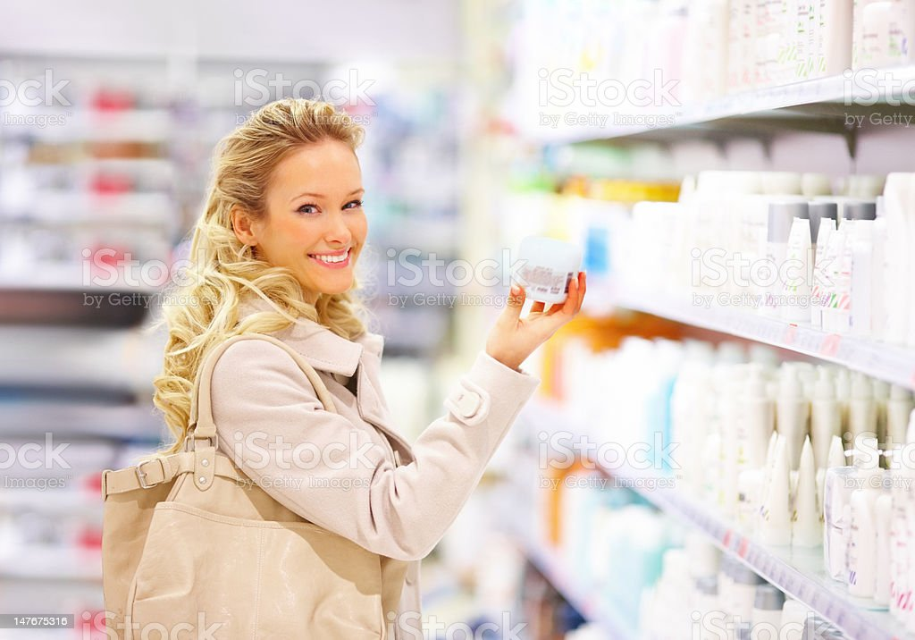 Happy young woman holding beauty product in mall royalty-free stock photo