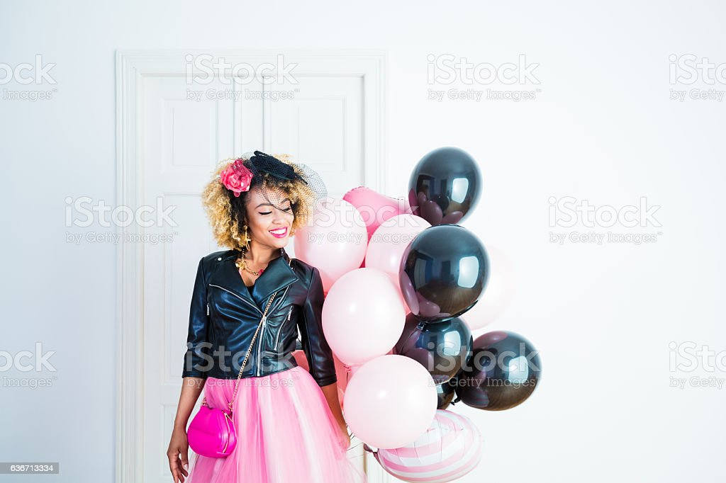 Happy young woman holding bunch of balloons stock photo
