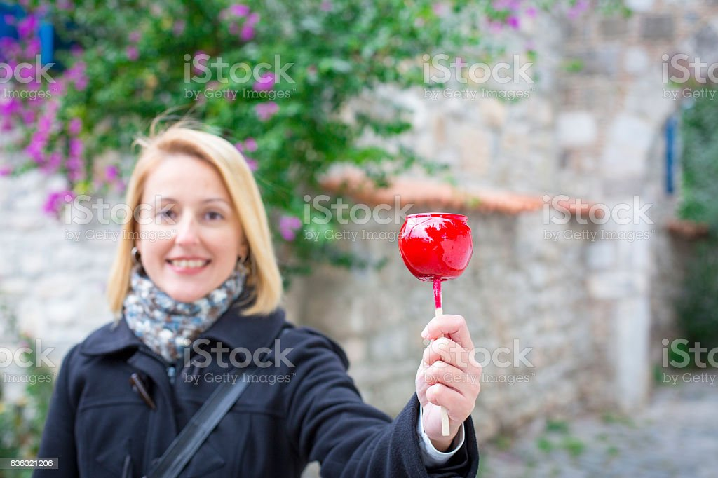 Happy young woman holding candy apple. stock photo