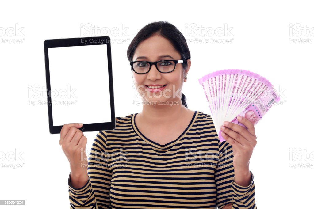 Happy young woman holding currency and tablet computer stock photo