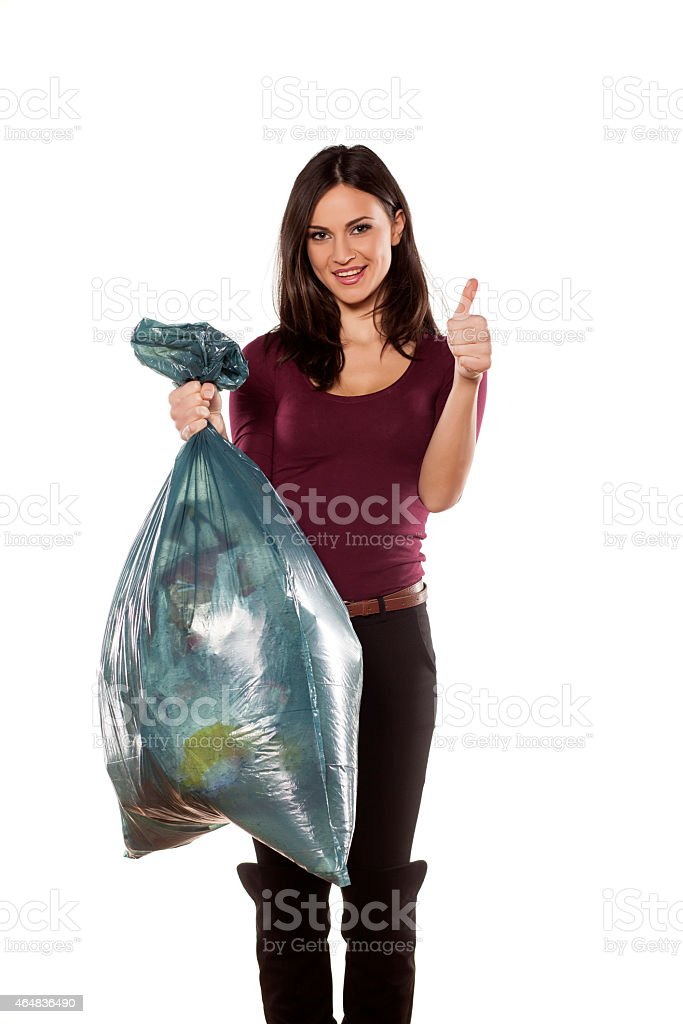 Happy young woman holding garbage bag and showing thumbs up stock photo