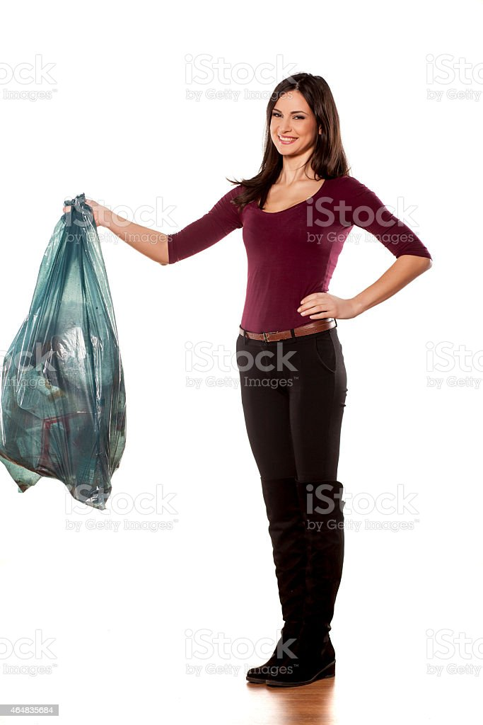 Happy young woman holding garbage bag on white background stock photo