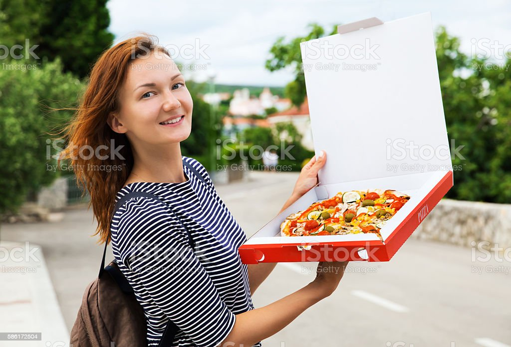 Happy young woman holding hot pizza in box stock photo