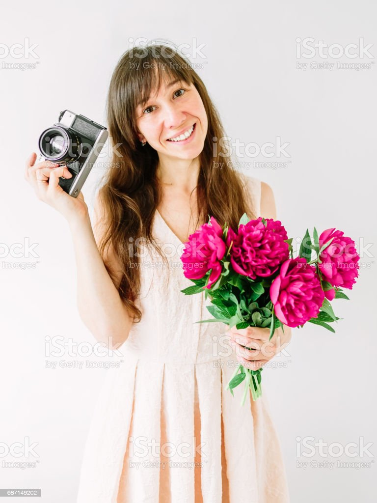 Happy young woman holding in hands bouquet of peonies and old vintage camera. Sweet romantic moment. Smiling woman stock photo