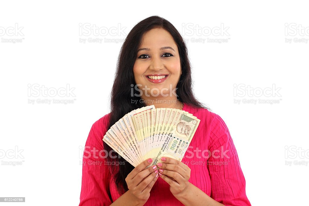 Happy young woman holding Indian rupee bank notes stock photo