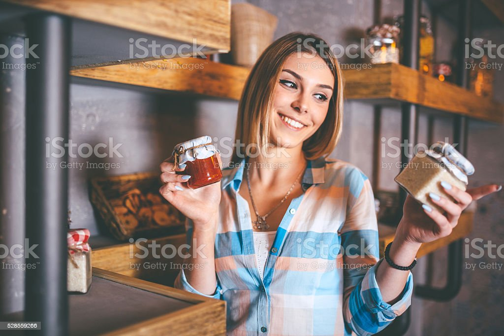 happy young woman holding jars with canned food stock photo