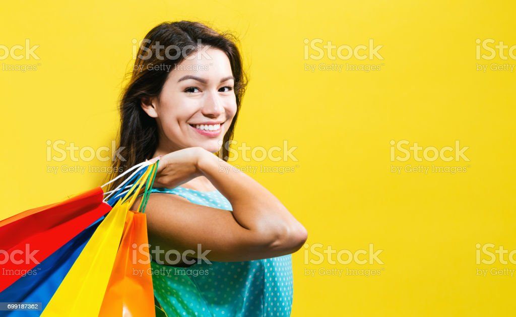 Happy young woman holding shopping bags stock photo