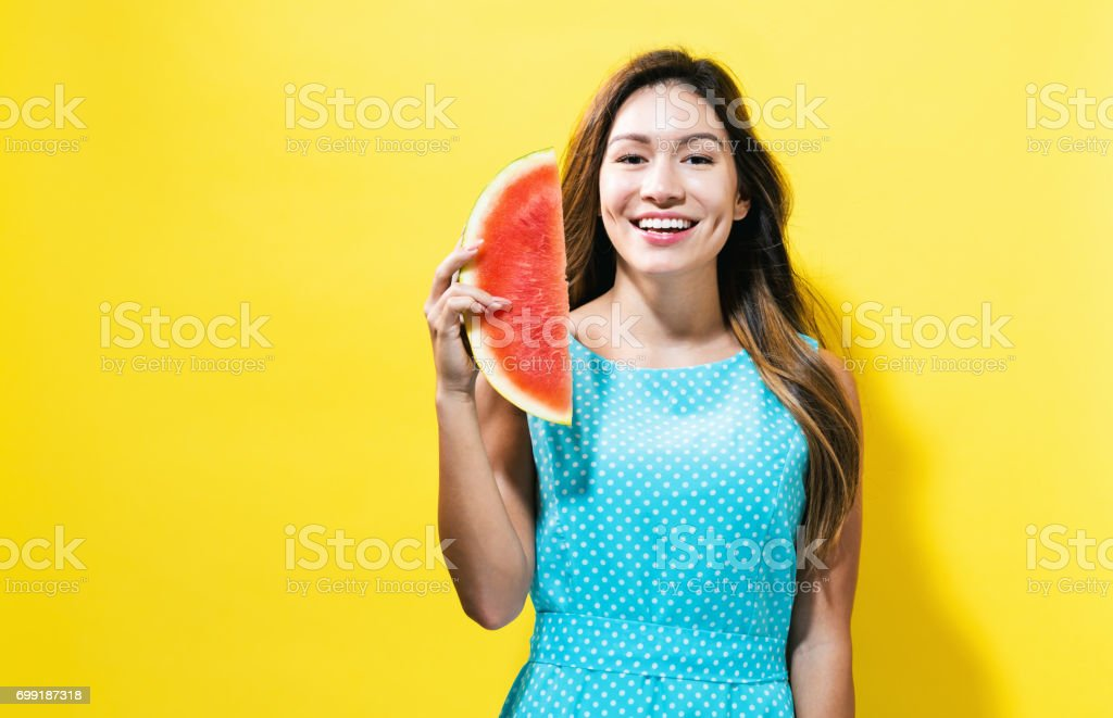 Happy young woman holding watermelon stock photo
