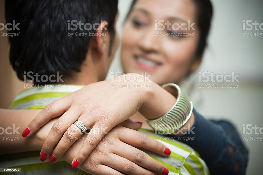Happy young woman hugging her spouse wearing engagement ring. stock photo