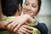 Happy young woman hugging her spouse wearing engagement ring.