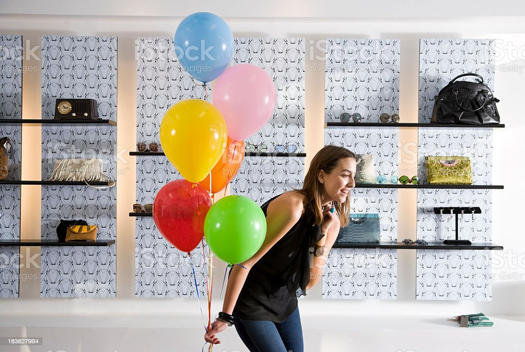 Happy young woman in boutique holding balloons royalty-free stock photo