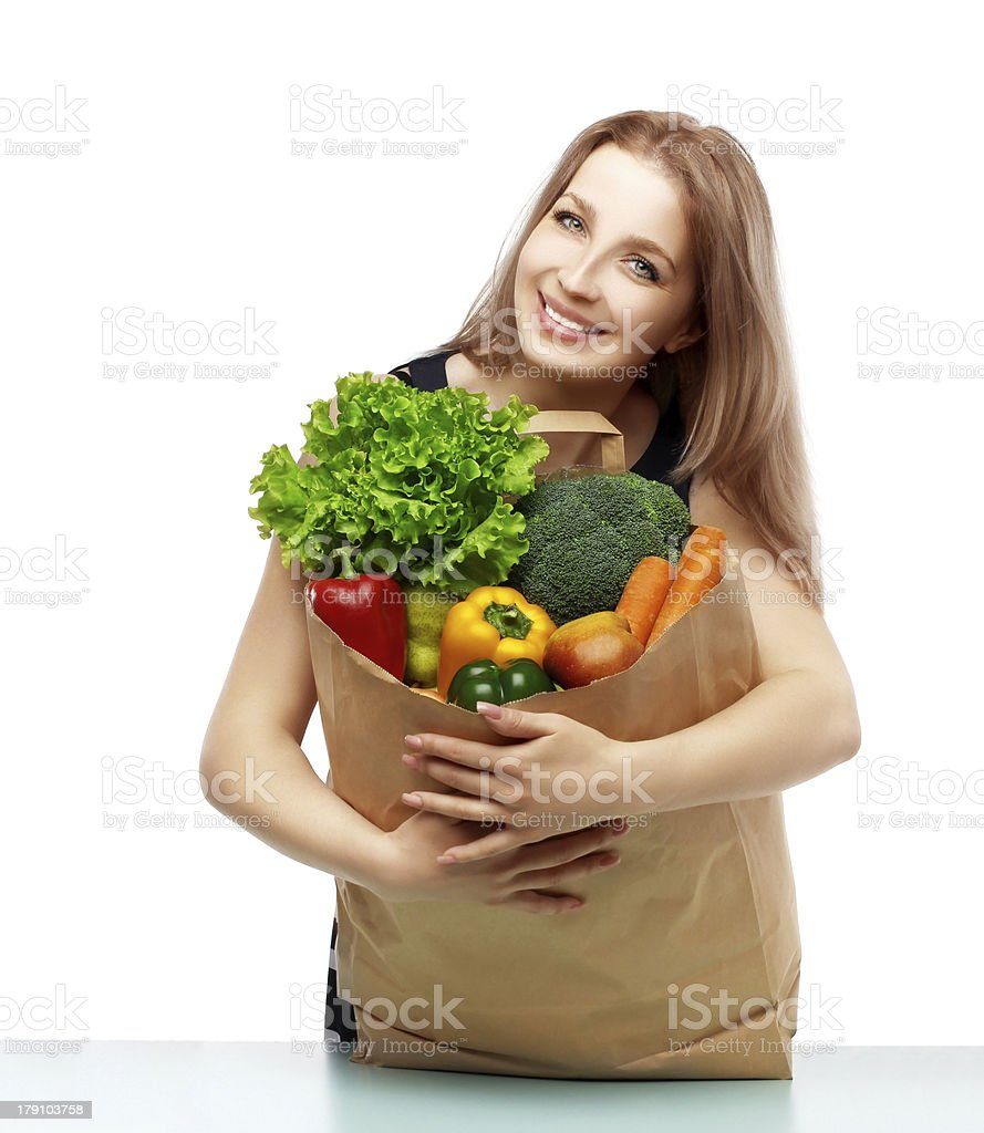 Happy young woman in dress holding grocery shopping bag royalty-free stock photo
