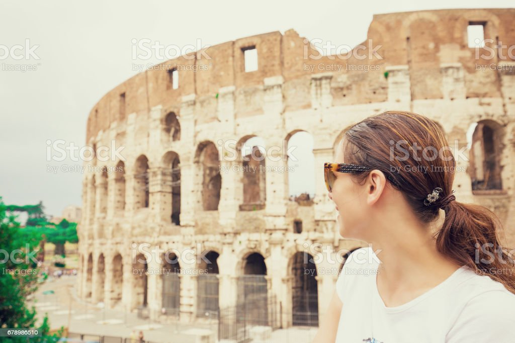 Happy young woman in front of colosseum in rome, Italy stock photo