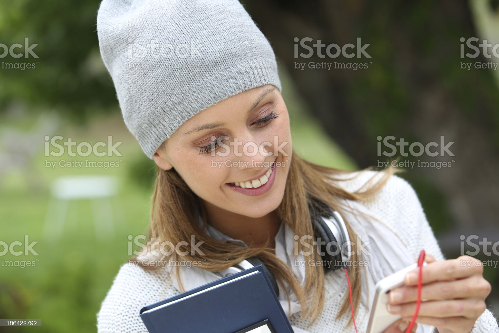 Happy young woman in garden using smartphone royalty-free stock photo
