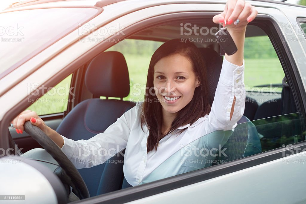 Happy young woman in her car portrait stock photo