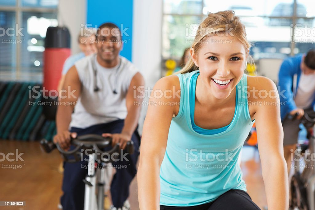 Happy young woman in her fitness cycling class royalty-free stock photo