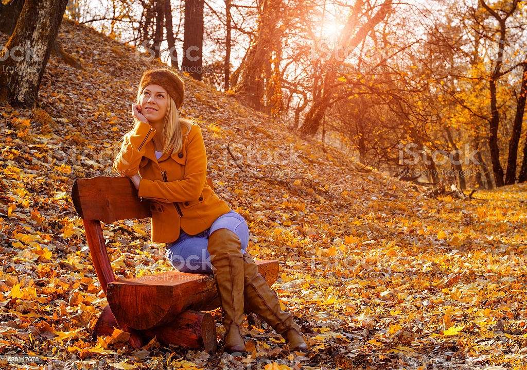 Happy young woman in park on sunny autumn day stock photo