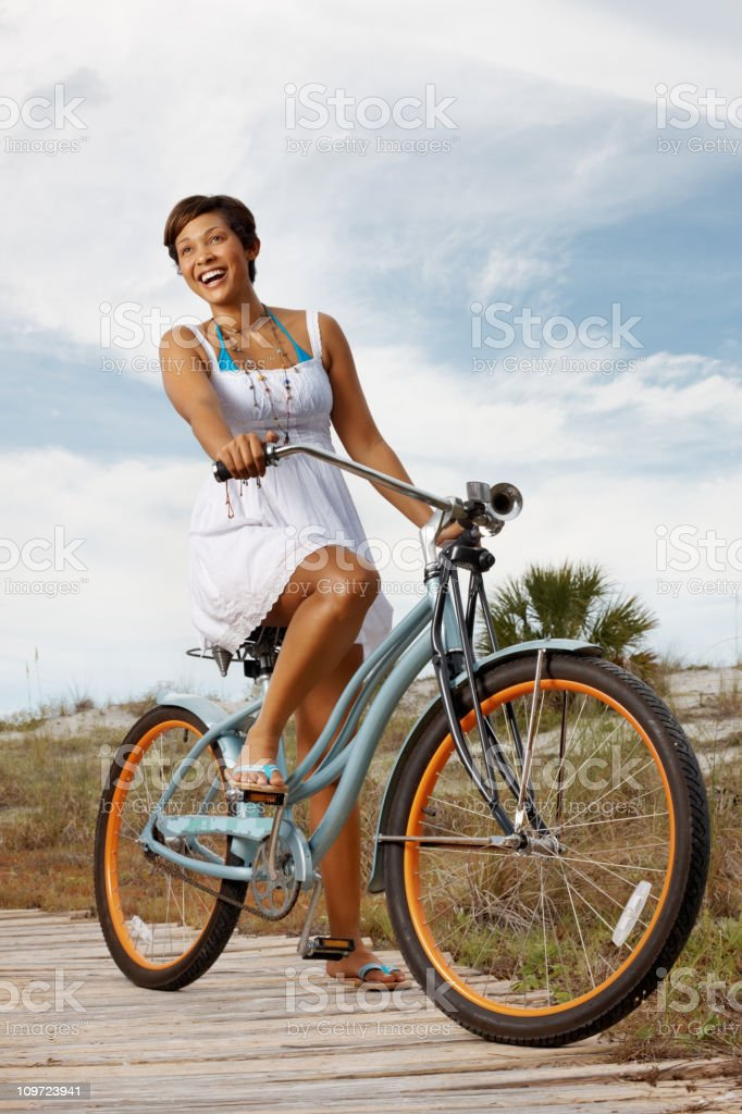 Happy, young woman in sundress riding bicycle on the beach royalty-free stock photo