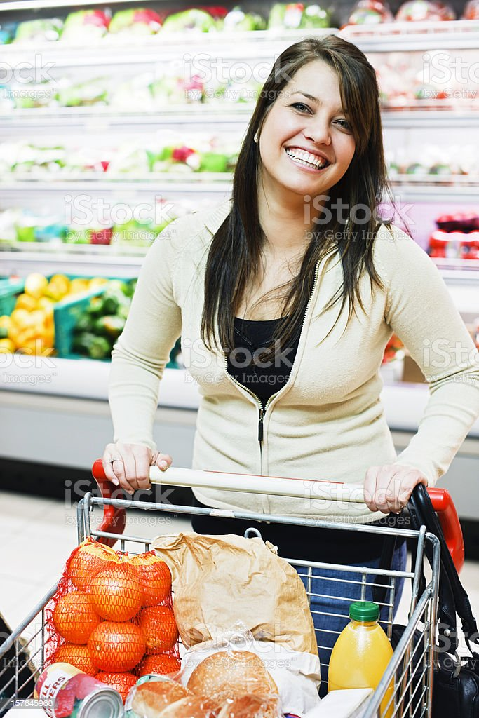 Happy young woman in supermarket fresh produce department royalty-free stock photo
