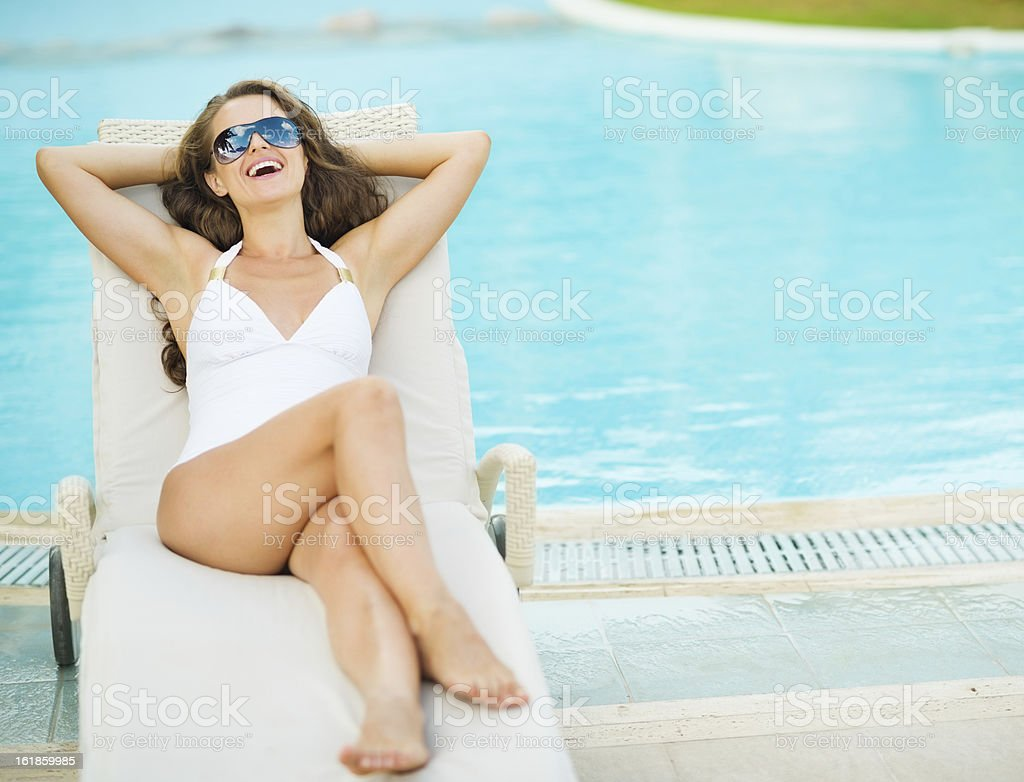 Happy young woman in swimsuit laying on chaise-longue poolside royalty-free stock photo
