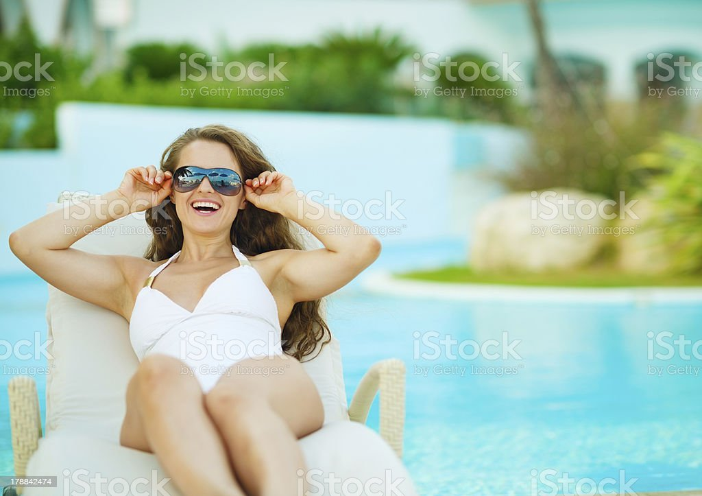 Happy young woman in swimsuit relaxing on chaise-longue royalty-free stock photo
