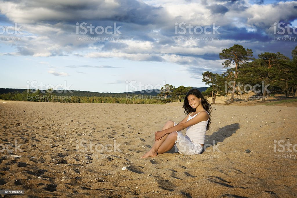 Happy young woman in white sitting on the beach. royalty-free stock photo