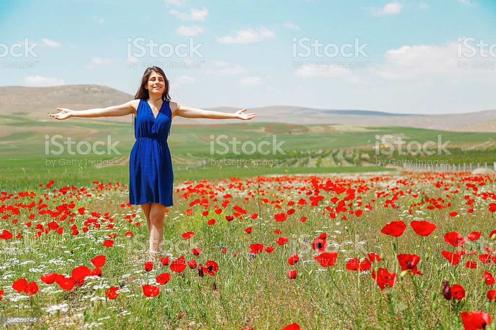 Happy young woman in wild flower field and sky. stock photo