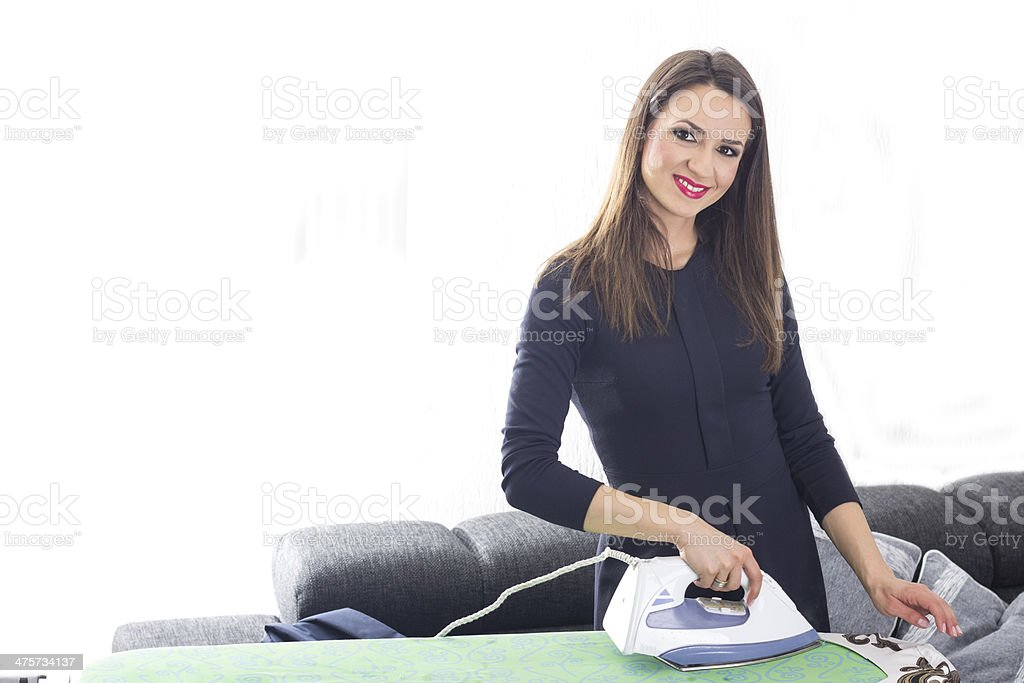 Happy young woman ironing on ironing board royalty-free stock photo