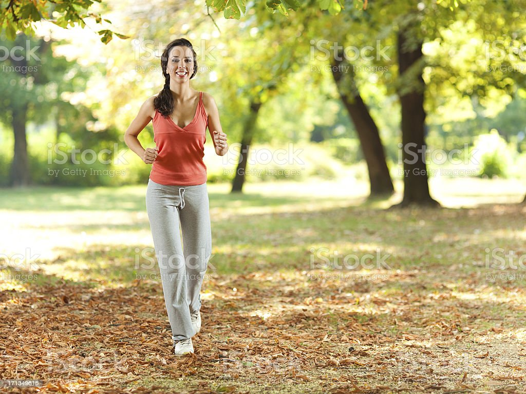 Happy young woman jogging stock photo