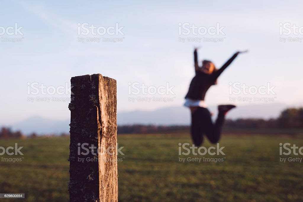 Happy young woman jumping in the nature stock photo