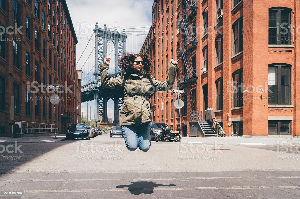 Happy Young Woman Jumping Near Manhattan Bridge in New York stock photo
