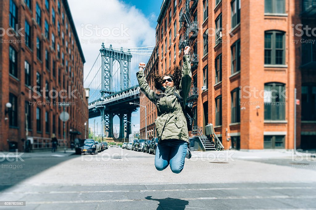 Happy Young Woman Jumping Near Manhattan Bridge in New York stock photo